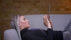 Zbliżenie krótkopęd młoda atrakcyjna caucasian modniś kobieta obraca kamera z dreadlocks używać pastylkę i zbiory wideo