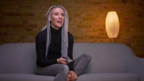 Zbliżenie krótkopęd młoda atrakcyjna caucasian modniś kobieta ogląda komedię na TV i dostaje śpiącego obsiadanie na zbiory