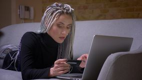 Zbliżenie krótkopęd młoda atrakcyjna caucasian modniś kobieta robi zakupy online z kredytem z dreadlocks używać laptop zbiory