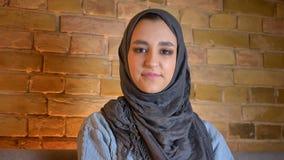 Zbliżenie krótkopęd młoda atrakcyjna muzułmańska kobieta patrzeje prosto przy kamerą indoors przy wygodnym domem w hijab zbiory