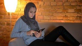 Zbliżenie krótkopęd młoda atrakcyjna muzułmańska kobieta używa ogólnospołecznych środki na telefonie przy wygodnym podczas gdy od zbiory wideo
