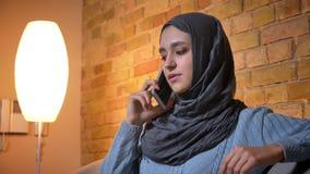 Zbliżenie krótkopęd młoda atrakcyjna muzułmańska kobieta w hijab ma rozmowę na telefonie podczas gdy siedzący na leżance zbiory