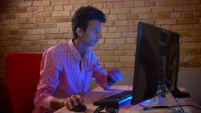 Zbliżenie krótkopęd młoda indyjska atrakcyjna samiec bawić się gra wideo na komputerze jest szczęśliwy w wygodnym indoors zbiory