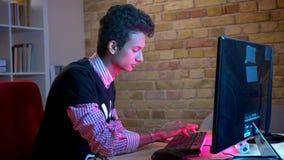 Zbliżenie krótkopęd młoda indyjska atrakcyjna samiec pisać na maszynie na komputerowym obsiadaniu indoors w wygodnym mieszkaniu z zbiory wideo