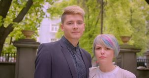 Zbliżenie krótkopęd młoda piękna modniś para opowiada radośnie ściskać kamerę w parku patrzeć outdoors i zbiory wideo