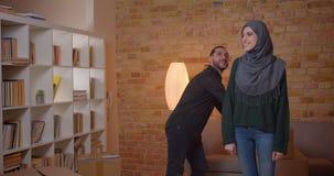 Zbliżenie krótkopęd młoda rozochocona muzułmańska para walkling w niedawno kupującego mieszkanie i sprawdza izbowego przytulenie  zdjęcie wideo