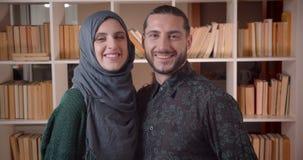 Zbliżenie krótkopęd młoda szczęśliwa muzułmańska para patrzeje prosto przy kamerą i ono uśmiecha się radośnie w niedawno kupujący zbiory wideo
