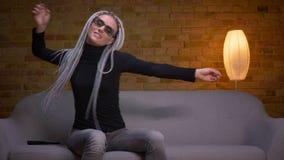Zbliżenie krótkopęd młodego atrakcyjnego caucasian modnisia żeński taniec i mieć zabawa z karaoke na TV obsiadaniu na zdjęcie wideo