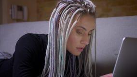 Zbliżenie krótkopęd młodego atrakcyjnego caucasian modnisia żeński uczeń studiuje online laptopu lying on the beach dalej z dread zdjęcie wideo