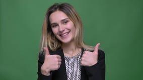 Zbliżenie krótkopęd młodego atrakcyjnego modnisia caucasian kobieta pokazuje aprobaty i uśmiecha się patrzeć prosto przy kamerą z zbiory wideo