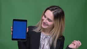 Zbliżenie krótkopęd młodego atrakcyjnego modnisia caucasian kobieta używa pastylkę i pokazywać błękitnego ekran kamera z zdjęcie wideo