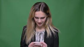 Zbliżenie krótkopęd młodego atrakcyjnego modnisia caucasian kobieta używa telefon z tłem odizolowywającym na zieleni zbiory