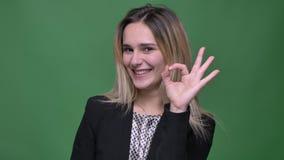 Zbliżenie krótkopęd młodego atrakcyjnego modnisia seansu ok caucasian żeński handsign i uśmiechać się patrzeć prosto przy kamerą zbiory wideo