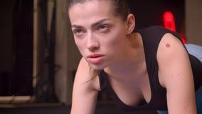 Zbliżenie krótkopęd młodej atrakcyjnej atlety żeńska pozycja w desce w gym indoors zbiory