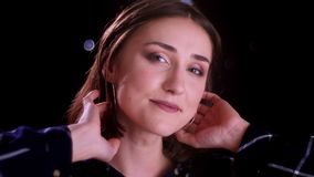 Zbliżenie krótkopęd młody ładny krótki z włosami żeński ono uśmiecha się seductively i patrzeć kamerę z bokeh światłami na zdjęcie wideo