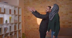Zbliżenie krótkopęd młody atrakcyjny arabski pary osiedlenie w niedawno kupującym mieszkaniu indoors zbiory
