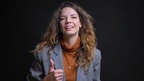 Zbliżenie krótkopęd młody atrakcyjny caucasian bizneswoman gestykuluje kciuk w górę i ono uśmiecha się podczas gdy patrzejący pro obrazy royalty free