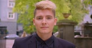 Zbliżenie krótkopęd młody atrakcyjny caucasian blondynka mężczyzna ono uśmiecha się radośnie patrzejący kamerę w parku outdoors zbiory wideo