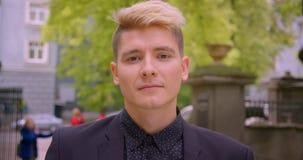 Zbliżenie krótkopęd młody atrakcyjny caucasian blondynka mężczyzna ono uśmiecha się szczęśliwie patrzejący kamerę w parku outdoor zbiory wideo