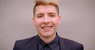 Zbliżenie krótkopęd młody atrakcyjny caucasian blondynka mężczyzna ono uśmiecha się szczęśliwie patrzejący kamerę z ścianą na tle zbiory wideo