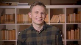 Zbliżenie krótkopęd młody atrakcyjny caucasian męski uczeń ono uśmiecha się i macha cześć patrzejący kamerę w szkoły wyższej bibl zbiory wideo