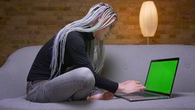 Zbliżenie krótkopęd młody atrakcyjny caucasian modnisia bizneswoman z dreadlocks pracuje na laptopu obsiadaniu na zbiory wideo