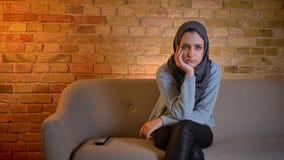 Zbliżenie krótkopęd młody atrakcyjny muzułmański żeński nastolatek ogląda melancholijnego film na TV podczas gdy siedzący na leża zdjęcie wideo