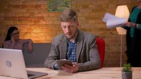 Zbliżenie krótkopęd młody biznesmen używa pastylkę przed laptopem i pokazywać zieleń ekran indoors w zbiory