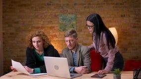 Zbliżenie krótkopęd młody caucasian biznesmen pracuje na laptopie i dyskutuje wykresy z dwa żeńskimi pracownikami zbiory wideo