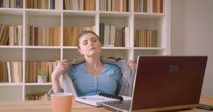 Zbliżenie krótkopęd młody caucasian bizneswoman używa laptopu gertting gorący i zmęczony w bibliotecznym biurze indoors zbiory