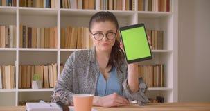 Zbliżenie krótkopęd młody caucasian bizneswoman używa pastylkę i pokazywać zieleń ekran kamera w bibliotecznym biurze zbiory