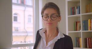 Zbliżenie krótkopęd młody caucasian bizneswoman wyszukuje na muzyka w szkłach i klimaty słuchaniu i pastylce zdjęcie wideo