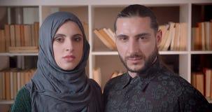 Zbliżenie krótkopęd młody muzułmański bizneswoman i biznesmen patrzeje prosto przy kamerą indoors w bibliotece zbiory wideo