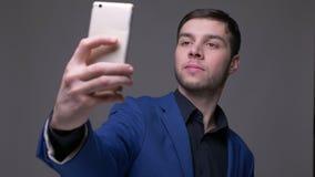 Zbliżenie krótkopęd młody przystojny caucasian mężczyzna bierze selfies na telefonie z tłem odizolowywającym na szarość zbiory