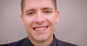 Zbliżenie krótkopęd młody rozochocony caucasian blondynka mężczyzna ono uśmiecha się szczęśliwie patrzejący kamerę z ścianą na tl zdjęcie wideo