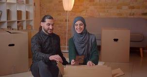 Zbliżenie krótkopęd młody szczęśliwy muzułmański pary obsiadanie na podłodze uśmiecha się radośnie advicing w niedawno kupującym  zdjęcie wideo