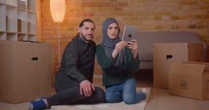 Zbliżenie krótkopęd młody szczęśliwy muzułmański pary obsiadanie na podłodze w niedawno kupującym mieszkaniu używać pastylki ono  zbiory