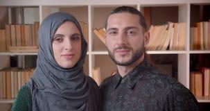 Zbliżenie krótkopęd młodzi muzułmańscy żeńscy i męscy ucznie patrzeje prosto przy kamerą w bibliotecznym uniwersytecie