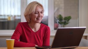 Zbliżenie krótkopęd ono uśmiecha się szczęśliwie indoors w wygodnym mieszkaniu starzejąca się caucasian kobieta ma wideo wzywa la zbiory wideo