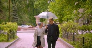 Zbliżenie krótkopęd opowiada radośnie młoda piękna modniś para trzyma parasolowego odprowadzenie wpólnie w kierunku kamery zbiory