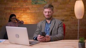 Zbliżenie krótkopęd otrzymywa powiadomienie na telefonie i ono uśmiecha się szczęśliwie indoors dorosły biznesmen używa laptop we zbiory wideo