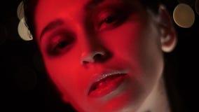 Zbliżenie krótkopęd patrzeje kamerę ładna żeńska twarz z oszałamiająco makeup z czerwonym neonowego światła i bokeh tłem zbiory