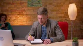 Zbliżenie krótkopęd patrzeje kamerę i ono uśmiecha się indoors dorosły biznesmen używa laptop bierze notatki w biurze zdjęcie wideo