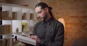 Zbliżenie krótkopęd patrzeje kamerę indoors młody atrakcyjny muzułmański brodaty męski uczeń czyta książkę w bibliotece zbiory