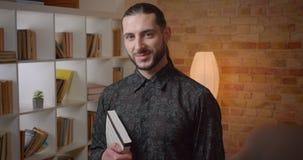 Zbliżenie krótkopęd patrzeje kamerę indoors młody atrakcyjny muzułmański brodaty męski uczeń trzyma książkę w bibliotece zbiory wideo