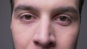 Zbliżenie krótkopęd patrzeje kamerę jest zamykający i otwiera z tłem odizolowywającym na szarość młoda męska twarz z oczami zdjęcie wideo