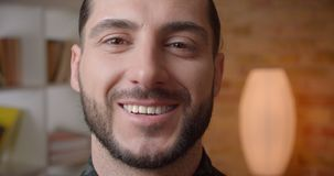 Zbliżenie krótkopęd patrzeje kamerę z uśmiechniętym wyrazem twarzy indoors młoda atrakcyjna muzułmańska brodata męska twarz zdjęcie wideo