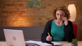 Zbliżenie krótkopęd pisać na maszynie na laptopie wzywa telefon i bierze notatki indoors w biurze dorosły bizneswoman zbiory wideo