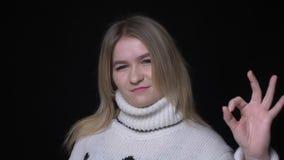 Zbliżenie krótkopęd potomstwo dosyć caucasian kobieta w puloweru seansu ok handsign i ono uśmiecha się patrzejący kamerę z zbiory