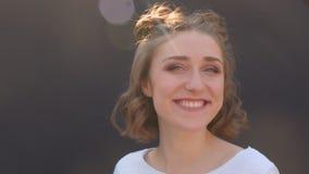 Zbliżenie krótkopęd potomstwo dosyć caucasian kobieta z włosianymi babeczkami uśmiechniętymi i śmiają się szczęśliwie pozować prz zbiory wideo